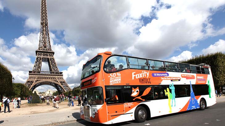Ônibus da hop on hop off em frente a Torre Eiffel